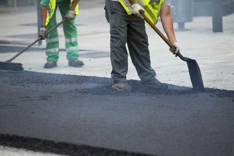 Worker operating asphalt paver machine during road construction